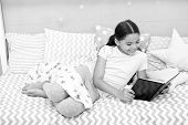 Fascinating story. Girl child lay bed with pillows read book. Kid prepare to go to bed. Time for evening fascinating story. Girl kid long hair cute pajamas relax and read fascinating story book. poster