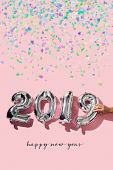 some confetti, a man forming the number 2019, as the new year, with some silvery number-shaped balloons and the text happy new year on a pink background poster