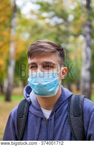 Young Man In The Flu Mask In The Autumn Park