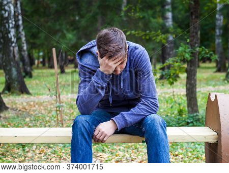 Sad Young Man Sit On The Bench In The Autumn Park