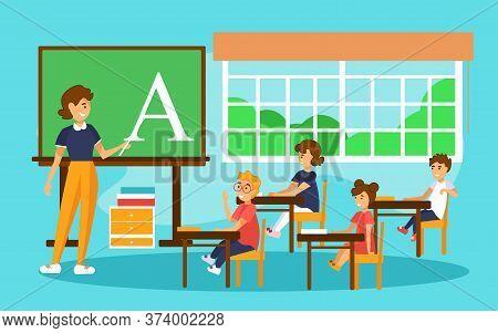 School Lesson In First Grade. Teacher Explaining Alphabet To Children.