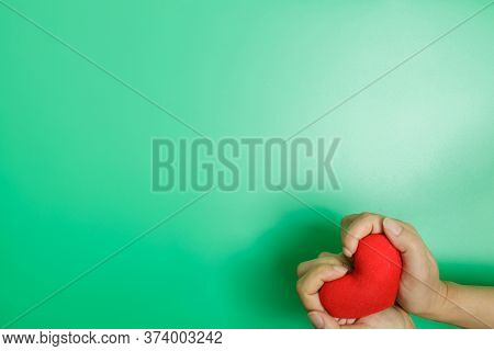 Adult Hands Holding Red Heart Isolated On Green Background, Health Care, Donate And Family Insurance