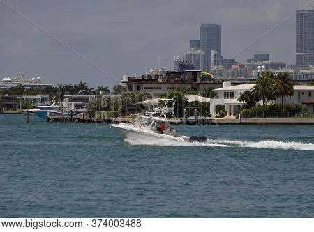 Upscale Sport Fishing Boat With Tower Bridge Cruising By Rivoalto Island In Miami Beach,florida With