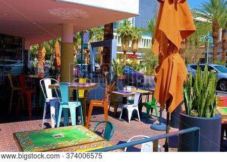 June 22, 2020 In Palm Springs, Ca:  Colorful Furniture Including Tables And Chairs On An Outdoor Pat