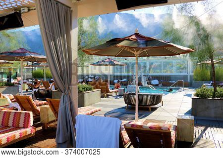 June 22, 2020 In Palm Springs, Ca:  Misters Blowing Out Mist From Above The Furnished Patio Area Wit