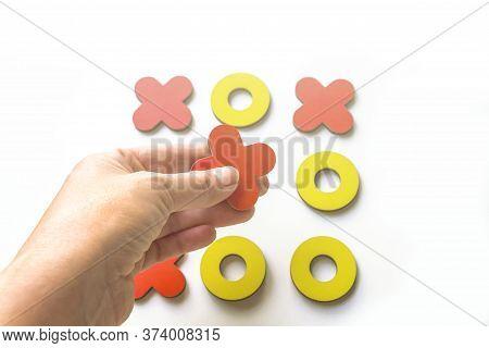 Kid Tic-tac-toe Wood Board Game On White Background. Female Hand Holds A Cross. Developmental Game.