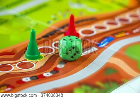 Colorful Play Figures And Plastic Chips With Dice On сolored Board. Board Games For Children And Adu