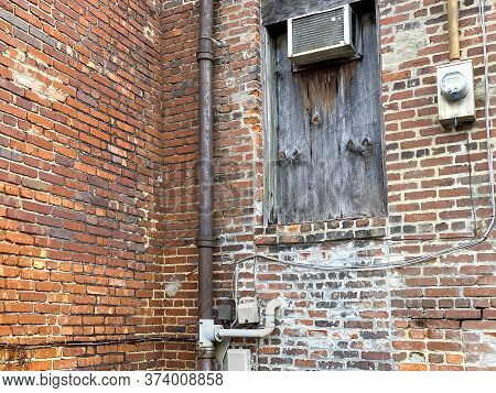 A Boarded Up Warehouse Alley Rusted Window On Old Brick Building