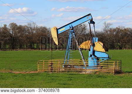 A Bright Painted Old Abandoned Oil Well Derrick In A Green Meadow Pasture