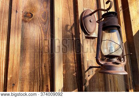 A Rusted Old Gas Lantern Hanging On An Old Log Cabin Shed Building