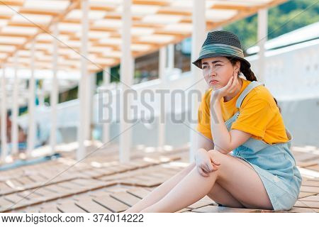 Emotion Of Sadness And Discontent. Portrait Of Young Woman In A Straw Hat Leaned On Her Hand In Disc