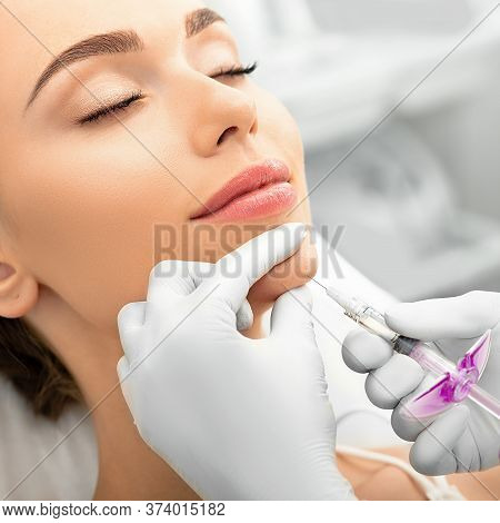 Woman During Skin Tightening Procedure, Injection Of Dermal Filler Into A Female Face. The Anti-agin