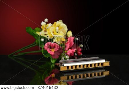 A Closeup Of A Harmonica With A Bouqet Of Flowers Over A Gradient Background.