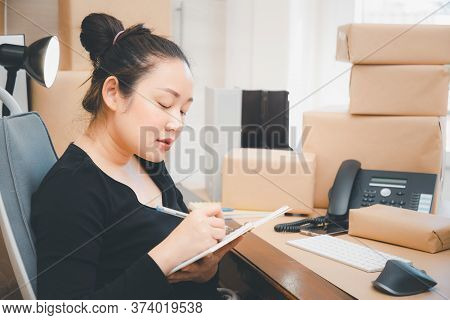 Asian Beautiful Woman Receiving Order Notebooks In Selling Products Online, Working At Home The Tech