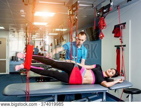 Physiotherapy. Suspension Training Therapy. Young Woman Doing Fitness Traction