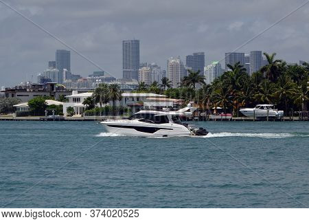 Small Luxury Motor Yacht Cruising On The Florida Intra-coastal Waterway Against A Background Of Covi