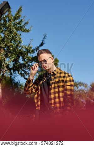 Urban Style Guy Poses Holding His Sunglasses Looking At Camera. Lifestyle Concept, Urban Style