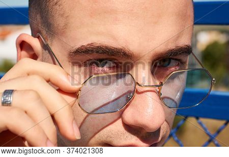Close Up Portrait Of A Guy Holding His Glasses. Green Eyes, Lifestyle Concept