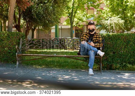Guy With A Mask Is Sitting In A Bench While He Writes With His Mobile. Lifestyle, Coronavirus