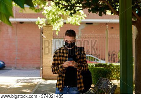 Guy With A Mask Writes A Massage With His Smartphone. Lifestyle, Coronavirus