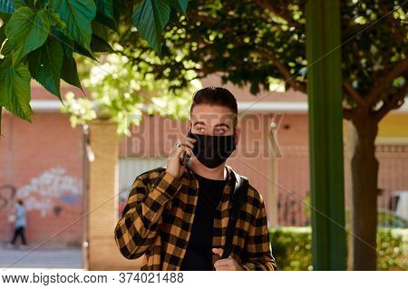 Guy Calls With His Smartphone With A Mask In A Park. Lifestyle, Coronavirus