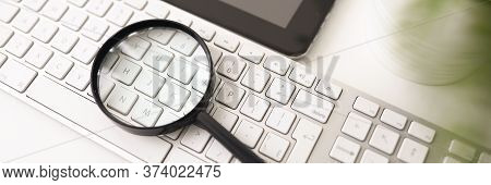Close-up Of Magnifier For Enlargement Lying On White Computer Keyboard. Workplace Interior. Modern T