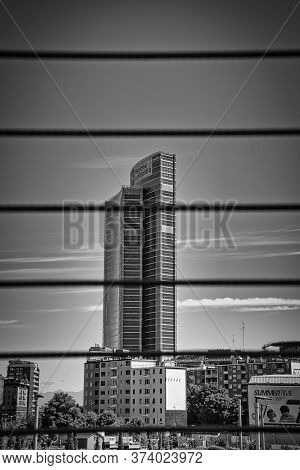Milan, Italy, 06.29.2020: View Of Lombardy Building, Palazzo Lombardia Through The Iron Wires Of A P
