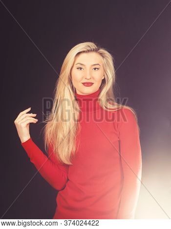 Optimistic Girl Touches Her Blond Hair. Lady In Red Blouse On Dark Background.