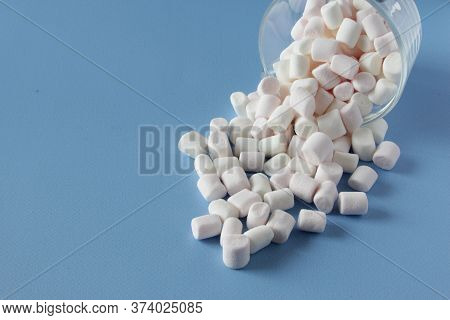 White Fluffy Marshmallows In Cup Isolated On Blue Background. Mini Marshmallows. Winter Food Backgro