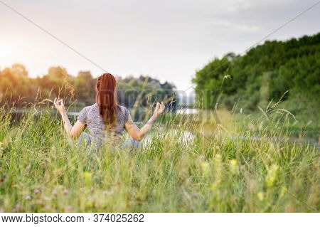 Woman Is Recovering In The Lotus Position Against The Backdrop Of Nature.