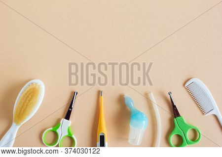 Flat Lay On Baby Care Items - Scissors, Hairbrushes, Nasal Aspirator And Thermometer- On Beige Backg