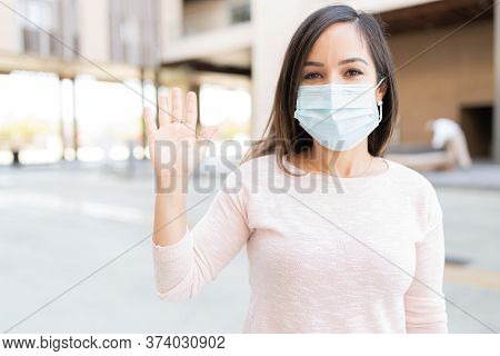 Caucasian Mid Adult Woman Waving Hand While Wearing Face Mask During Coronavirus Outbreak In City