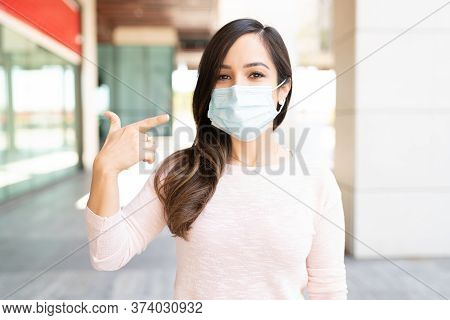 Caucasian Mid Adult Woman Gesturing While Wearing Face Mask In City