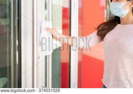 Caucasian Mid Adult Woman Holding Door Handle With Tissue Paper During Coronavirus Outbreak