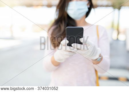 Midsection Of Mid Adult Woman Texting Through Mobile Phone During Coronavirus Crisis
