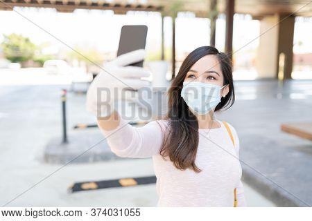 Mid Adult Woman Taking Selfie Through Smartphone In City During Coronavirus Outbreak