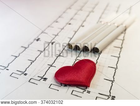 A Red Heart On A Background Of Cigarettes Lies On A Printout Of The Results Of A Cardiogram. Symbol