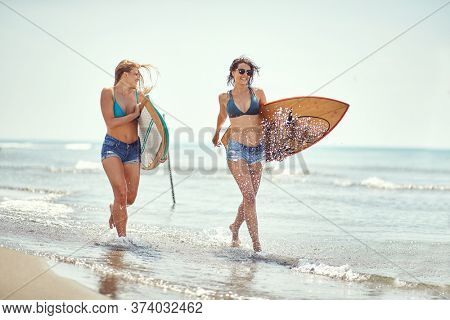 Young woman running to surfing on the beach.Sexy girls with  surfboard at summer.
