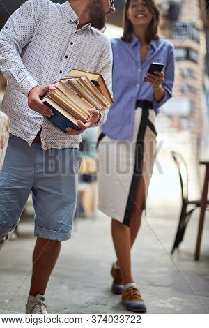 old-fashioned man carrying heavy pile of books at library, looking at female with her cell phone in her hands with e-books. books versus e-books concept