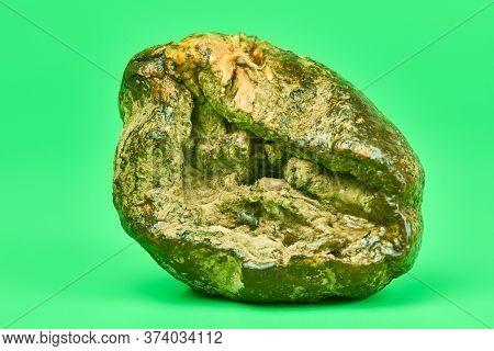 Rotten Lemon, Green Background. Mold Putrefied Fruit Yellow And Green Lemon. Unsuitable Inedible Foo