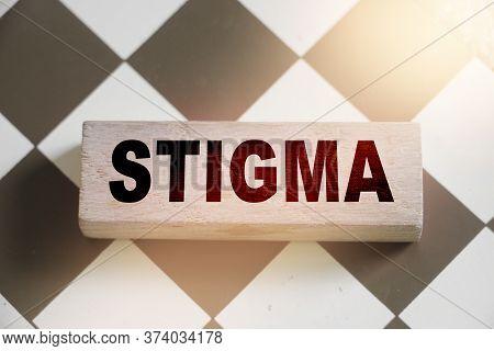 Stigma Word On Wooden Building Block Put On Chessboard. Discrimination Social Concept