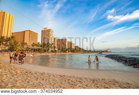Waikiki Hawaii - November 6 2014; Beachgoers On Beach And In Water In Afternoon Sun With Rock Protec