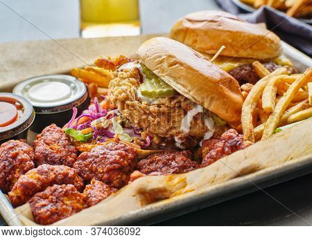 fried chicken sandwich and cheeseburger in tray with fries and boneless wings