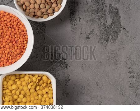 Red, Yellow And Green Lentils On A Gray Background.