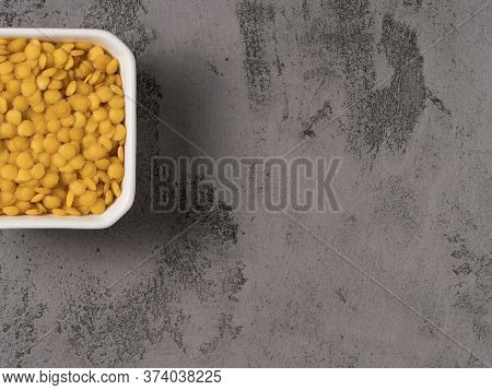Yellow Lentils On A Gray Background. Close-up.
