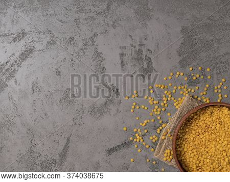Yellow Lentils In Ceramic Bowl On Sackcloth. The Gray Background.