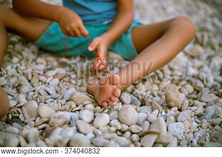 Toddler Boy Sitting On Pebble Beach With Colorful Strings Attached To His Toes As He Makes A Knotted