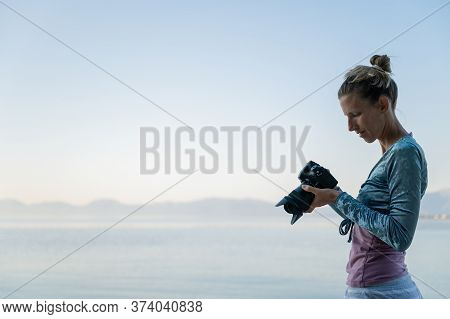 Young Female Photographer Standing By The Beautiful Calm Morning Sea Checking Photos And Setting On