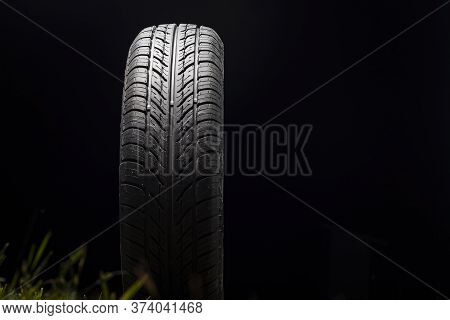 Car Tire In Dark Color. Night Shooting. The Tread Is Summer. Light Falls From Above