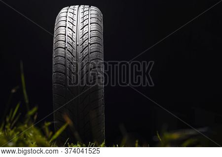Car Tire In Dark Color. Night Shooting. The Tread Is Summer. Light Falls From Above.